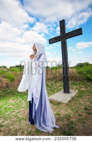 Beautiful Elf Girl Near The Big Cross, Are Praying.