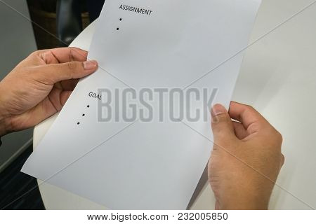 Business Concept - Close Up Employee Hold Mock Up Paper Of Assignment And Goals For Performance Revi