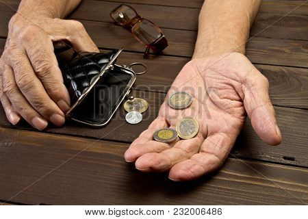 An Elderly Person Holds The Coins Over The Old Empty Wallet.hands Of Beggar With Few Coins. The Conc