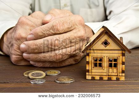 Old Man Hands And A Model Home With The Coins On The Table .the Concept Of Mortgages And Bank Loans,