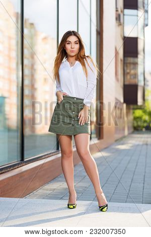 Young fashion woman standing at the window in a city street. Stylish female model in white short and short skirt outdoor