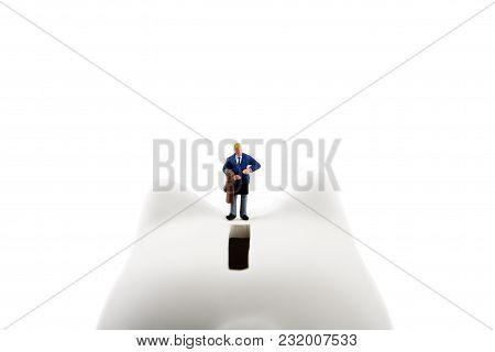 Businessman Figurines On A Piggybank. Money, Business, Corruption And Economy Concept.