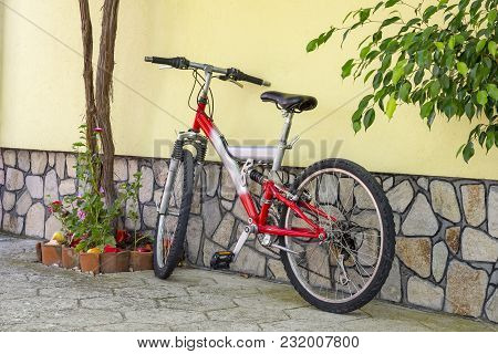 A Bicycle Stands Against The Wall In The Yard Of A House . Conceptual Image Of A Healthy Lifestyle A