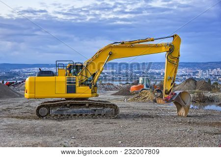 Evening, Yellow Excavator With Shovel  At Construction Site