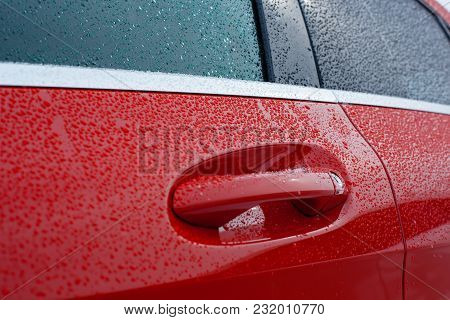 Close-up Red Car Handle And Door Covered With Water Drops.