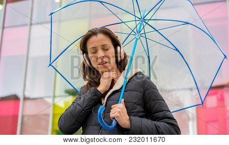woman with fever and discomfort from the cold and winter flu, girl in the street with a transparent umbrella with signs of illness
