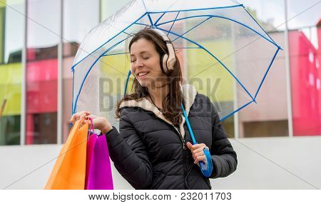 showing purchase. Brown-haired woman shopping. carry colorful bags with purchases and a transparent umbrella