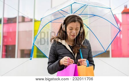 lifestyle buying. Brown-haired woman shopping. carry colorful bags with purchases and a transparent umbrella