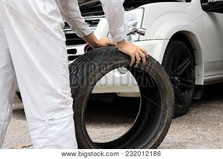 Selective Focus On Hands Of Professional Mechanic In Uniform Holding Wrench And Tire At The Repair G