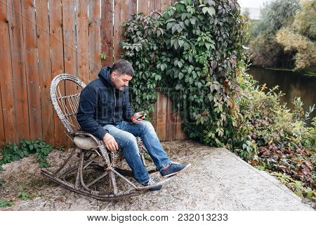 Handsome Man Relax In Vintage Rocking-chair With Phone In Garden