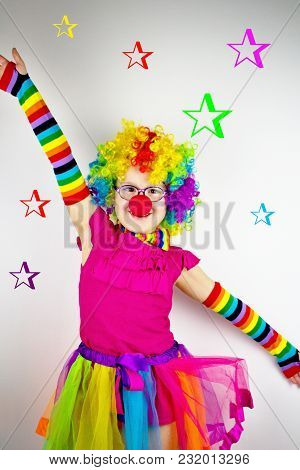 Little Girl In Clown Costume In Front Of White Background With Colorful Stars.little Girl With Glass