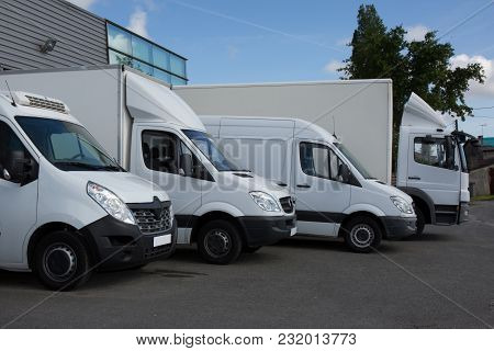 Row Of White Delivery And Service Van, Trucks And Cars In Front Of A Factory And Warehouse Distribut