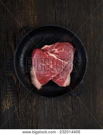 Fresh Raw Beef Meat Steaks In The Black Plate On Black Wooden Background