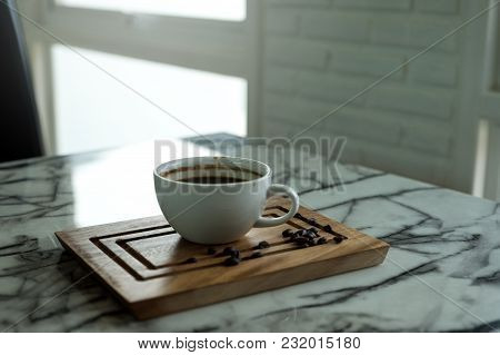 Closeup Image Of A Cup Of Hot Coffee And A Wooden Saucer On The Table In Cafe