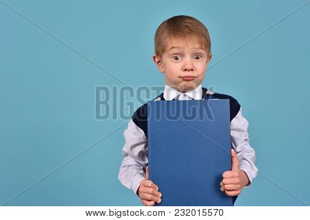 A Cheerful Teenager On A Blue Background. Schoolboy With A Book. Striving For Knowledge.