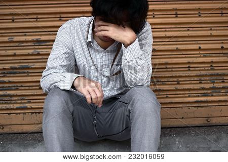 Front View Of Sad Depressed Young Asian Business Man Covering Face With Hands.