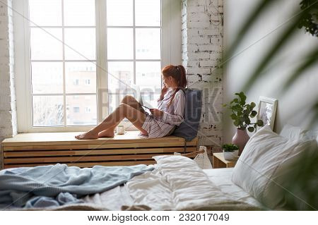 Sideways Shot Of Cheerful Young Female In Nightsuit Sitting Barefooted On Wide Windowsill With Porta
