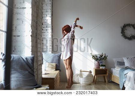 Full Lenght Shot Of Attractive Young Redhead Female In Long Striped Shirt Standing Barefooted On Her