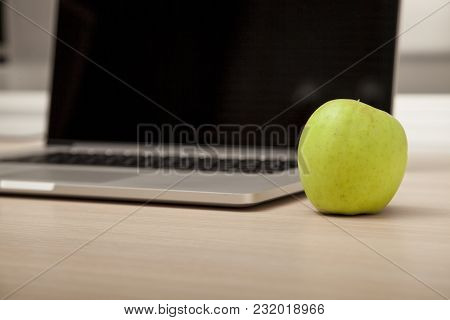 Conceptual Photo, An Green Apple On A Laptop As A Symbol Of Knowledge And Science