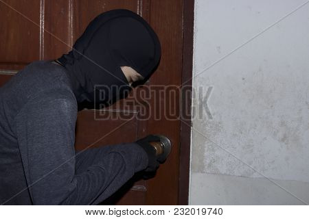 Masked Burglar With Balaclava Entering And Breaking Into A House At Night Time. Crime Concept.
