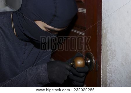 Masked Thief With Balaclava Entering And Breaking Into A House At Night Time. Crime Concept.