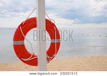 Life Ring Hanging On A Pillar, On The Beach Against The Sea