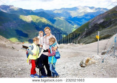 Happy Mother With Little Baby Girl And Two Kids Boys Travelling In Backpack. Hiking Adventure With T