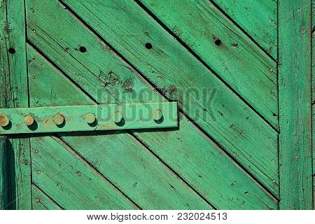 A Fragment Of An Old, Painted, Wooden Green Door With Hinges