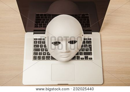 Conceptual Photo, Mask On A Laptop As A Symbol Of A Hacker Attack, View From Above