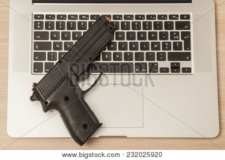 Conceptual Photo, Weapon On A Laptop As A Symbol Of Organized Crime Operating On The Internet