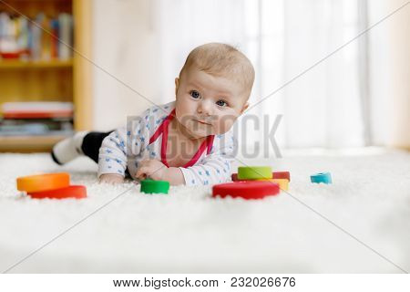 Cute Adorable Newborn Baby Playing With Colorful Wooden Rattle Toy Ball On White Background. New Bor