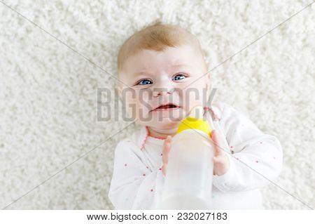 Cute Adorable Ewborn Baby Girl Holding Nursing Bottle And Drinking Formula Milk. First Food For Babi