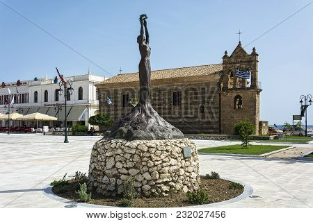 Greece, Zakynthos Island-june 17, 2016: Statue Of Glory On The Background Of The Church Of St. Nicho