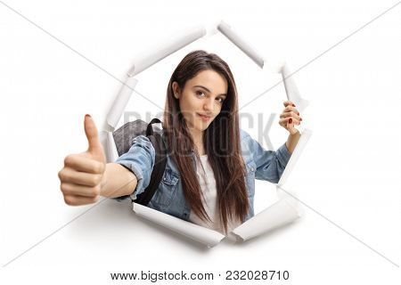 Female teenage student breaking through paper and making a thumb up gesture