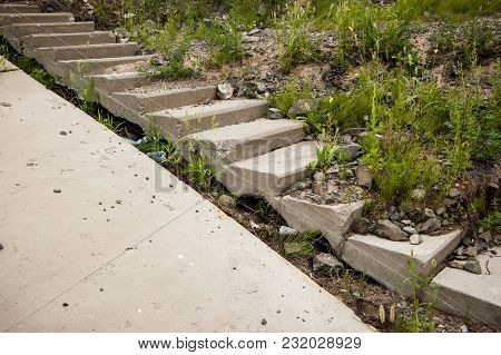 An Old Abandoned Cement Staircase Overgrown With Grass Leading Down. The Concept Of Decay And Destru