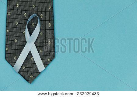 Cyan / Blue Tape As Symbol Of Men Illness Prostate Cancer Lying On Black Men Tie On Cyan / Blue Back