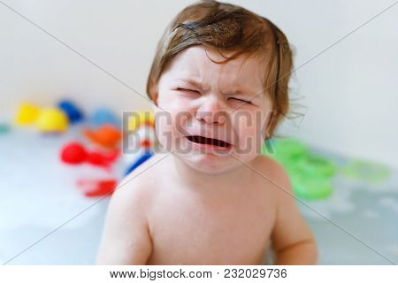 Cute Adorable Sad Baby Girl Taking Foamy Bath In Bathtub. Crying Toddler Playing With Bath Rubber To