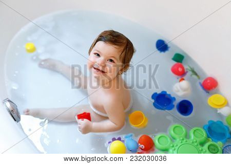 Cute Adorable Baby Girl Taking Foamy Bath In Bathtub. Toddler Playing With Bath Rubber Toys. Beautif