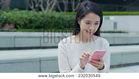Woman sending sms on smart phone at outdoor