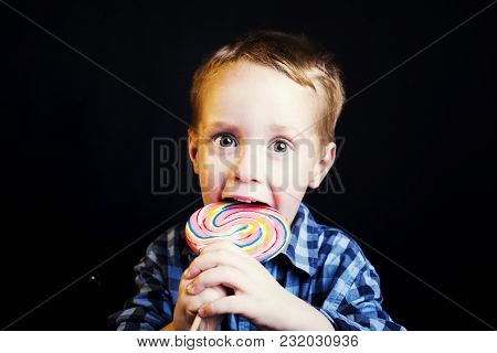 Young Boy Holding Lollipop On Black Background.