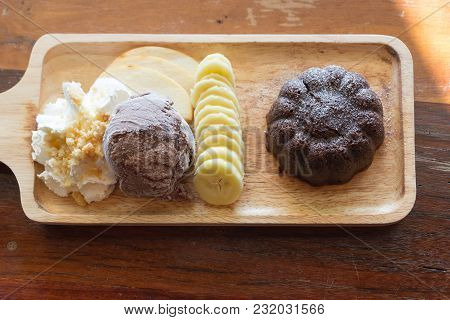 Chocolate Lava Cake Set, With Chocolate Icecream Banana Apple Fruit And Whipped Cream On Wood Table