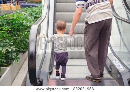 Backside Of Cute Little Asian 18 Months / 1 Year Old Toddler Baby Boy Child And Dad Holding Hands On