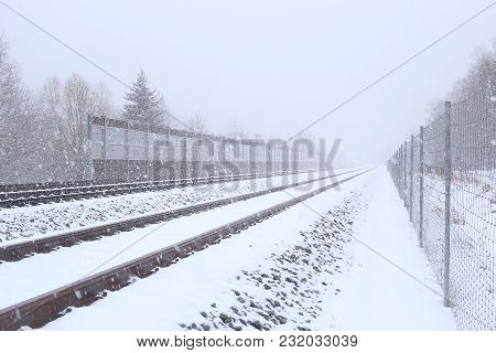 Snowy Railway With Noise Damping Wall In Winter. Rail Baltica Railroad Protective Fences.