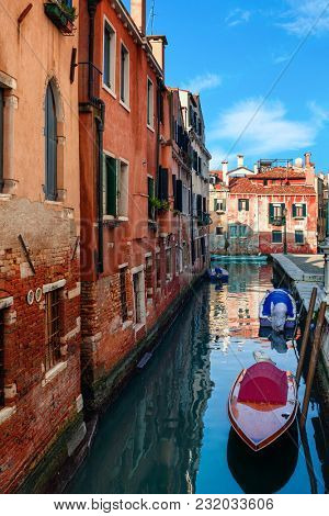 Boats on narrow canal along old brick houses in Venice, Italy ( vertical composition).