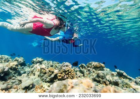 Underwater photo of family mother and kids snorkeling in a clear tropical water at coral reef