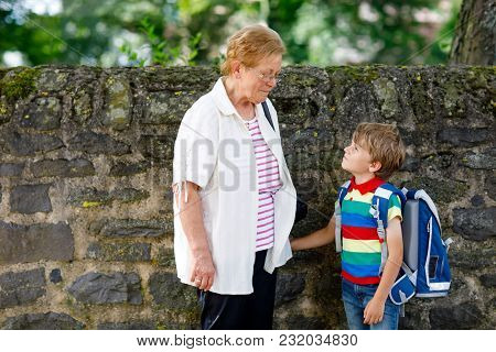 Grandmother Taking Child, Kid Boy To School. Pupil Of Primary School Go Study. Senior Woman Holding