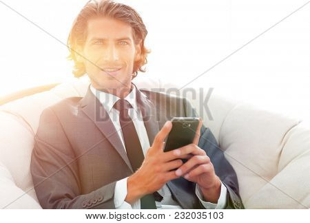 successful business man with a smartphone sitting in a comfortable chair