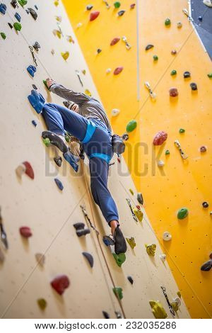 Climber On Wall.young Man Practicing Rock Climbing On A Rock Wall Indoors