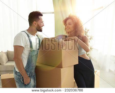 Loving couple standing next to boxes