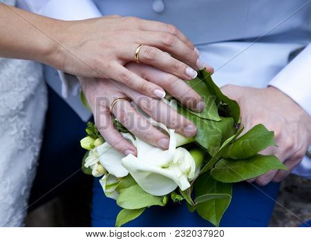 Detail Of The Hands Of The Newlyweds Wearing Their Beast Ring Costume And Bouquet
